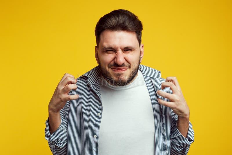 年轻人愤怒使男性姿态困恼,用偶然蓝色衬衣表现出消极情感,穿戴,摆在反对黄色 库存图片