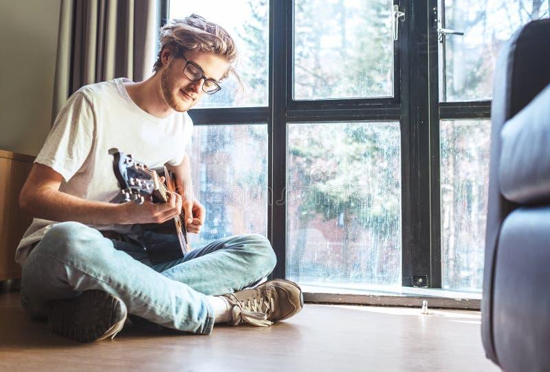 年轻人戏剧中间射击在吉他的坐地板  免版税库存照片