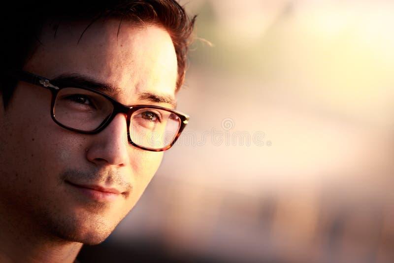 年轻人戴着眼镜接近的画象  库存图片