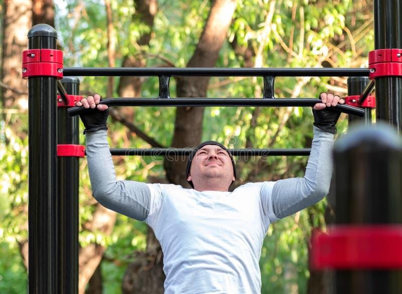 年轻人执行体育行使在酒吧的引体向上 在开发背部肌肉的力量的街道上的训练, 库存图片