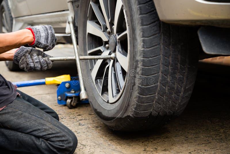 年轻人技工佩带的手套,汽车修理,使用修理的板钳的改变的轮胎在路的车轮泄了气的轮胎,运输和 库存图片