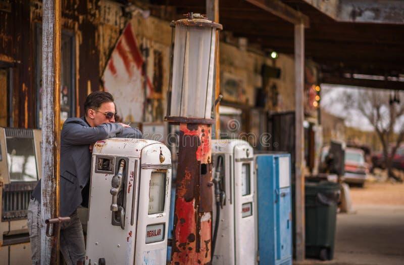 年轻人抽香烟在葡萄酒气泵 免版税库存图片