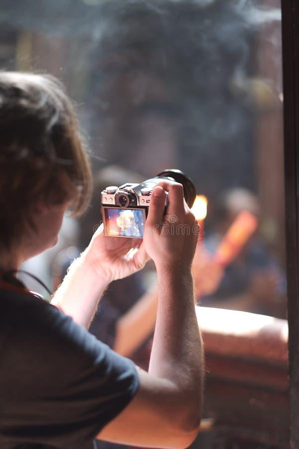 年轻人拍在佛教寺庙的照片 免版税库存照片