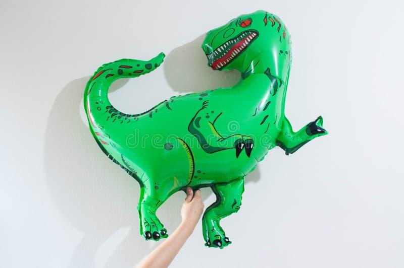 年轻人拿着一个绿色膨胀的恐龙气球 库存图片