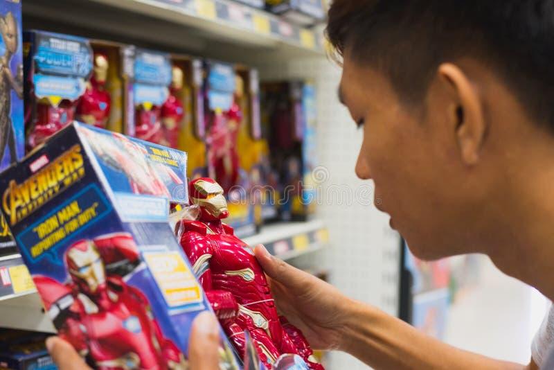 年轻人拿着一个铁人模特的盒子 免版税库存照片