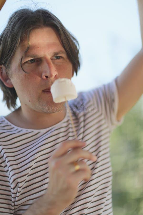 年轻人拿着一根木棍子用蛋白软糖 免版税库存照片
