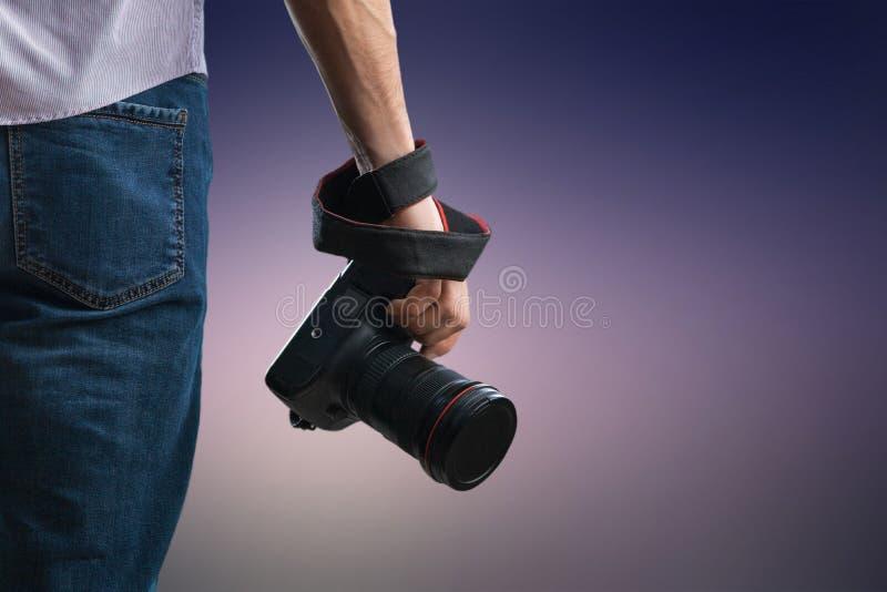 年轻人拿着黑现代数码相机 免版税图库摄影