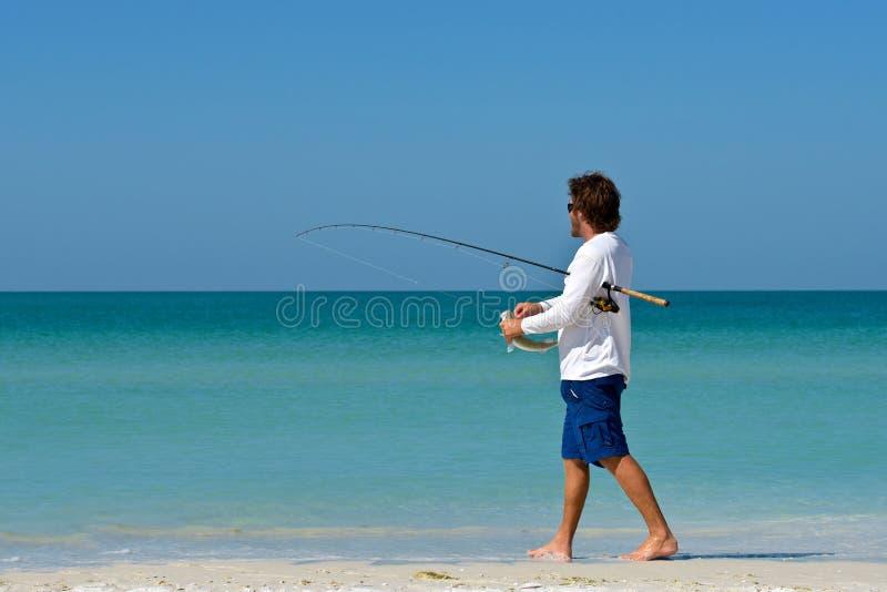 年轻人捕鱼 库存照片