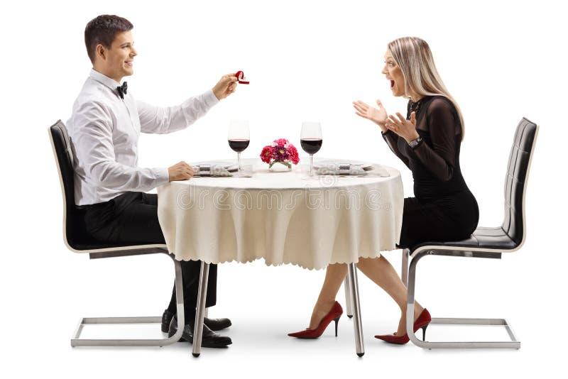 年轻人提出与圆环的婚姻对年轻女人在餐馆桌上 库存照片