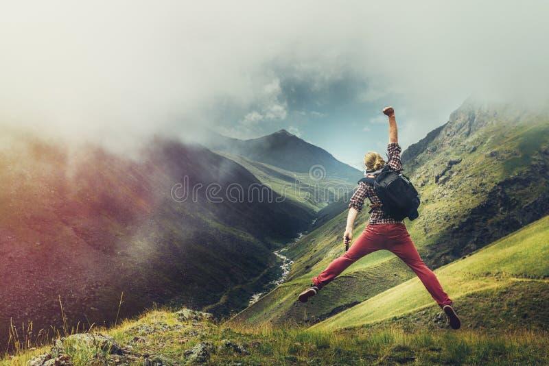 年轻人旅客在山背景跳并且享用 库存照片