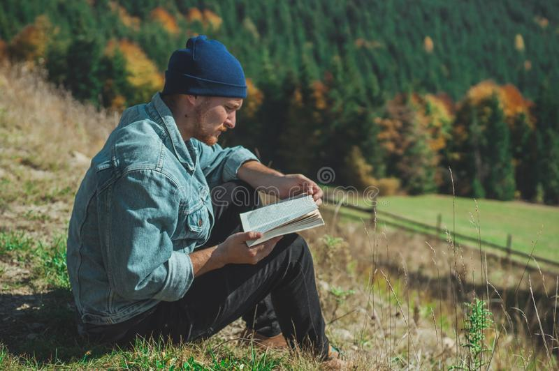 年轻人旅客看书,在背景暑假和生活方式概念的室外山 免版税图库摄影
