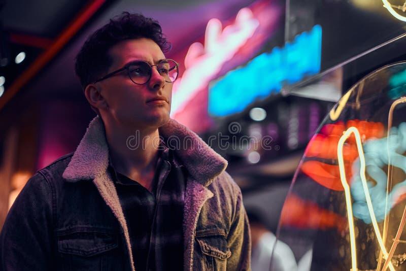 年轻人时兴地在晚上穿戴了在街道的身分 有启发性牌,氖,光 库存照片