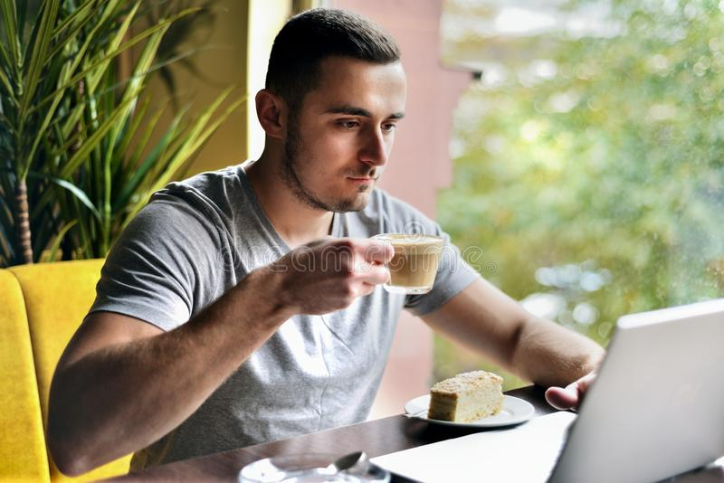 年轻人是咖啡馆工作的自由职业者在膝上型计算机后 咖啡饮用的人 免版税库存照片