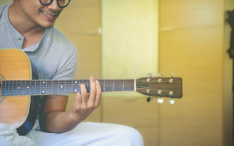 年轻人是松弛与他的吉他 免版税图库摄影