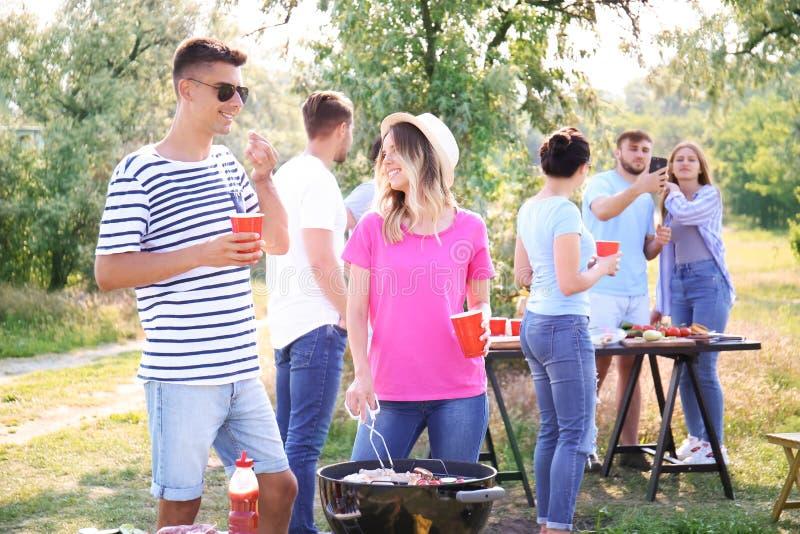 年轻人有烤肉聚会在公园 免版税库存图片