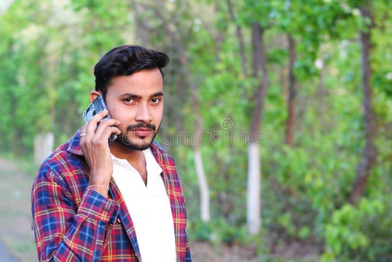 年轻人模型谈话与他的手机在森林里 库存图片