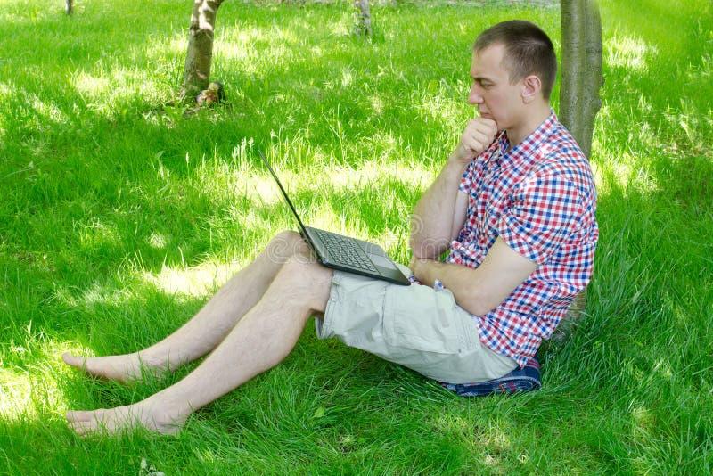 年轻人沉思地与一台膝上型计算机在庭院里坐草 室外工作 免版税库存照片