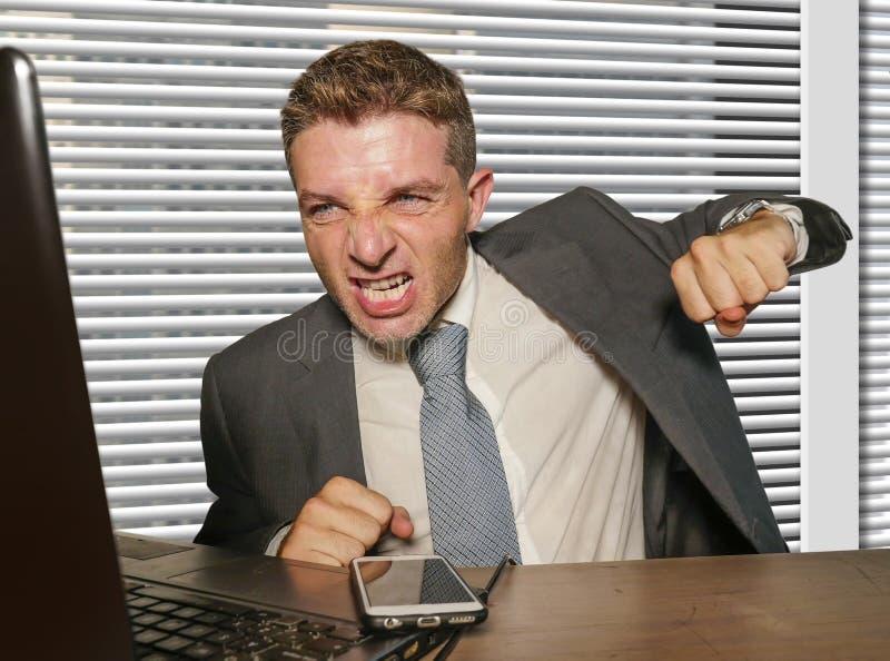 年轻人注重了并且淹没了在衣服和领带猛击的手提电脑沮丧和恼怒的工作的商人在办公桌 库存图片
