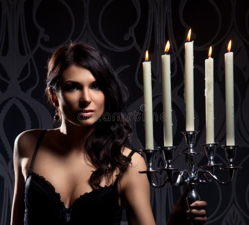 年轻人深色的妇女藏品蜡烛的纵向 库存照片