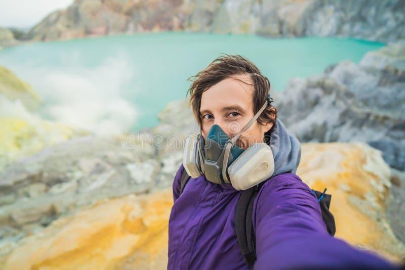 年轻人游人在印度尼西亚语做站立在伊真火山火山或Kawah伊真火山的火山口的边缘的一selfie 免版税库存照片