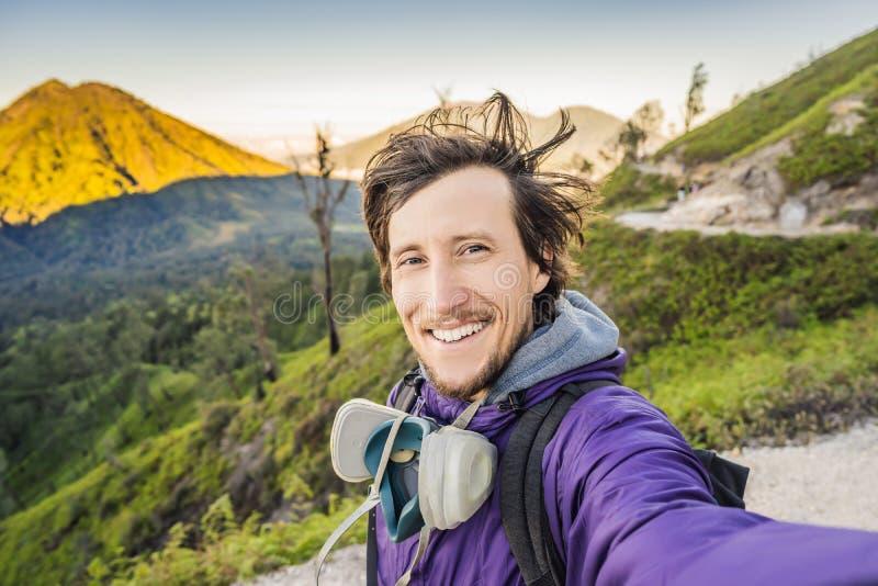 年轻人游人在绿色山做一selfie有宏伟的视图由艰苦跋涉对伊真火山的山路 免版税库存图片