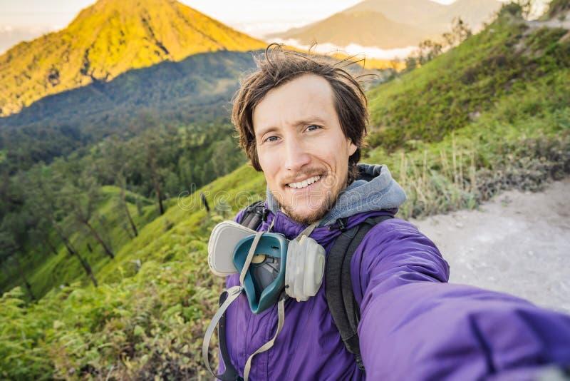 年轻人游人在绿色山做一selfie有宏伟的视图由艰苦跋涉对伊真火山的山路 库存图片