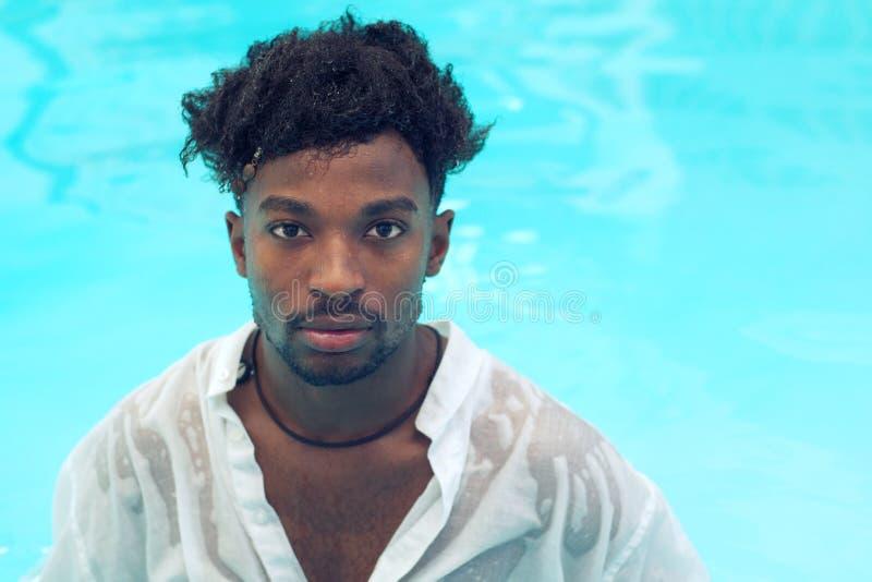 年轻人湿衬衣水池水游泳假期 免版税库存照片