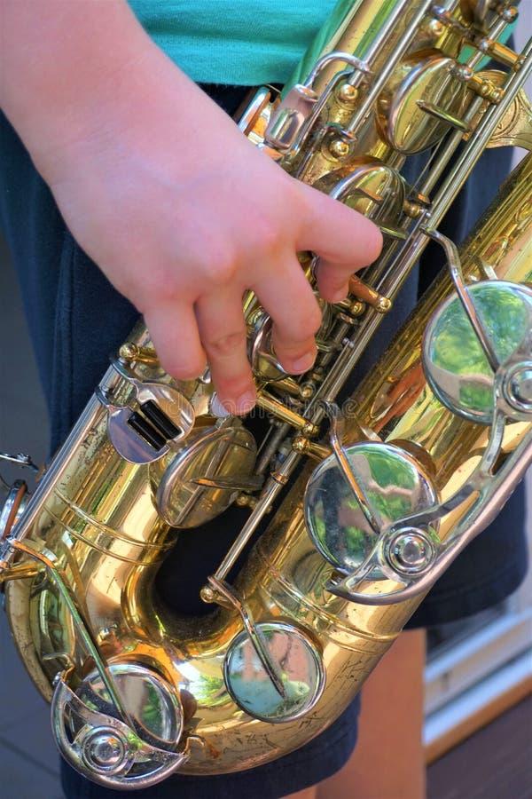 年轻人演奏关于萨克斯管的笔记用赤手 库存图片