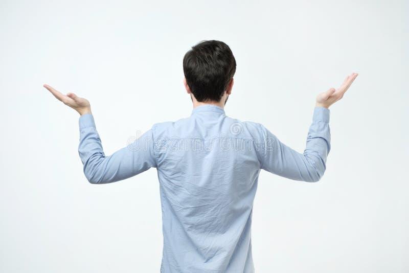 年轻人演播室射击蓝色衬衣身分的回到照相机 库存图片