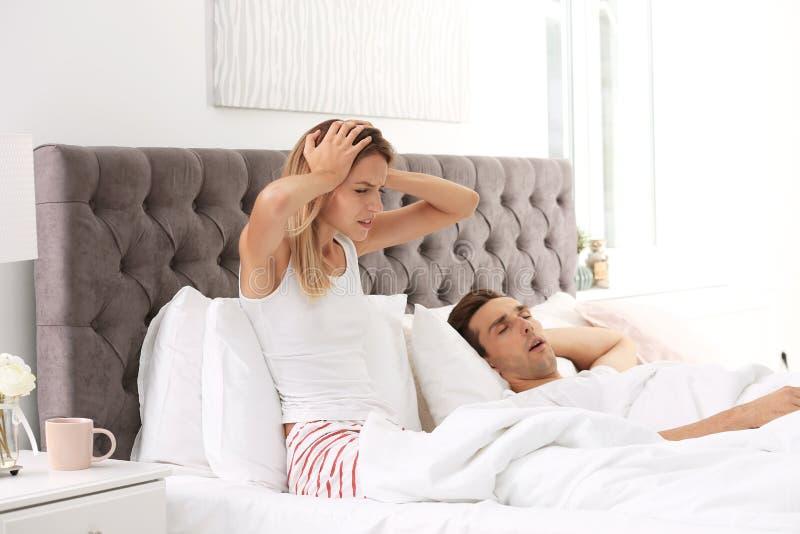 年轻人激怒了在家坐在与枕头的床上的妇女 打鼾的问题 免版税库存图片