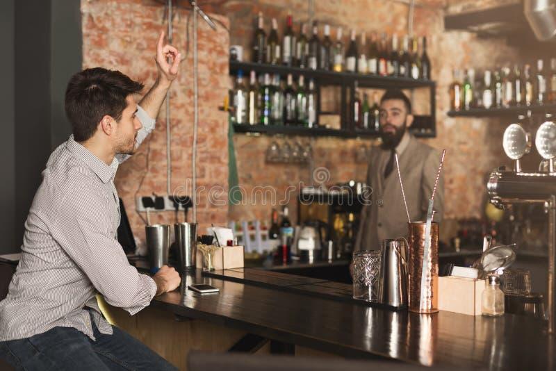 年轻人点在酒吧的啤酒 免版税库存照片