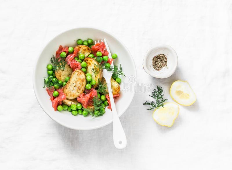 年轻人烘烤了土豆、熏制鲑鱼、绿豆和莳萝沙拉在轻的背景 免版税库存图片