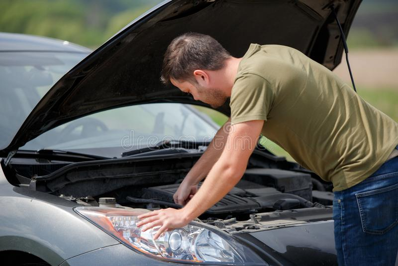 年轻人照片在残破的汽车旁边的有开放敞篷的 免版税库存图片