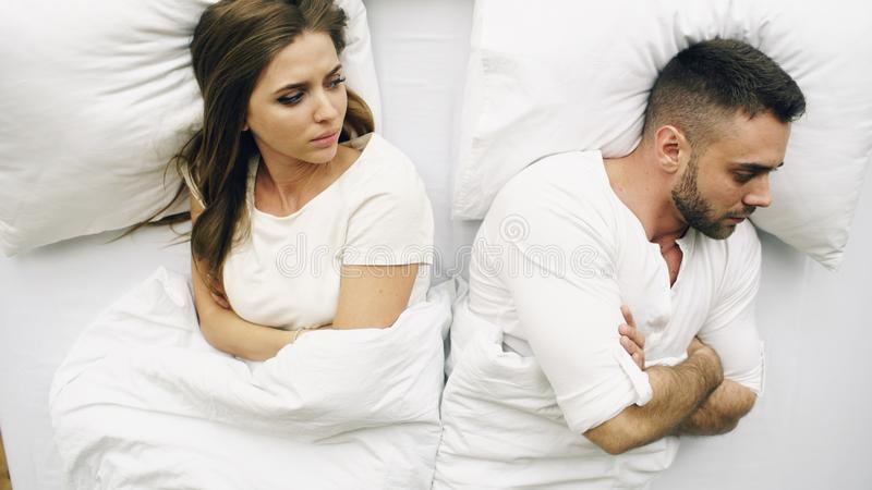 年轻人生气的夫妇顶视图恼怒在床上在家有问题在争吵以后和 库存图片