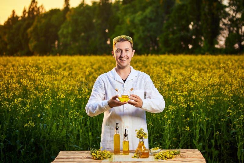 年轻人生物学家或农艺师审查菜子油的质量在强奸领域的 r 免版税库存照片