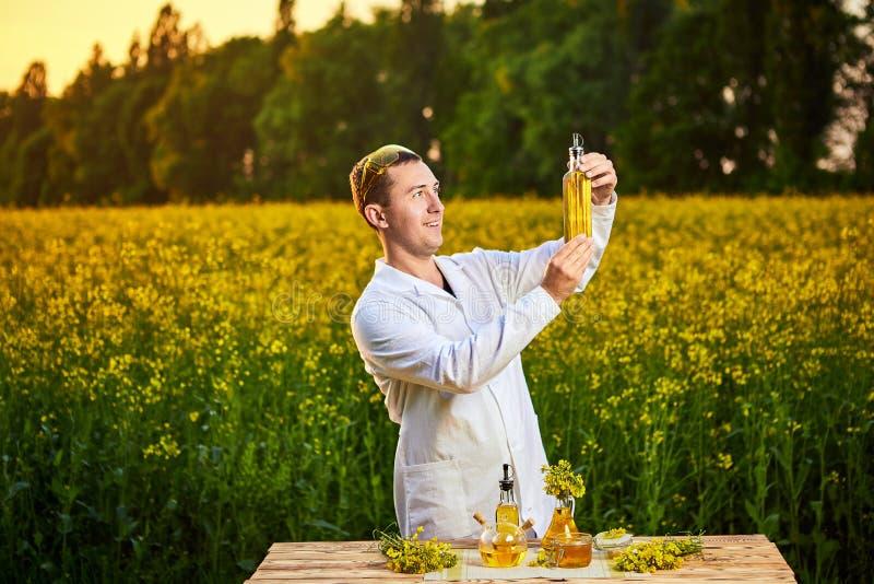 年轻人生物学家或农艺师审查菜子油的质量在强奸领域的 r 库存照片
