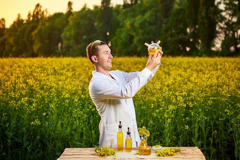 年轻人生物学家或农艺师审查菜子油的质量在强奸领域的 r 免版税库存图片