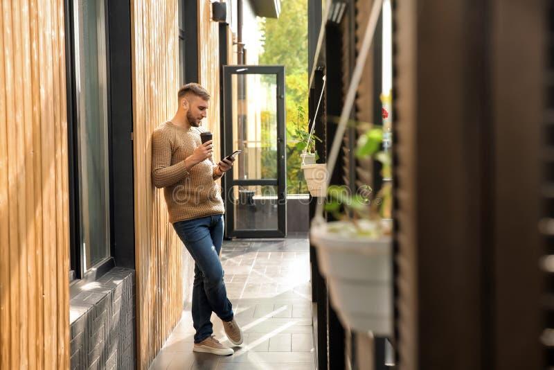 年轻人用手机饮用的咖啡户外 库存图片