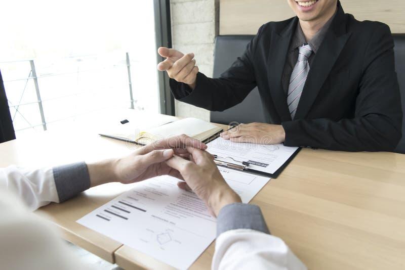 年轻人由雇主采访 穿着黑衣服解释工作申请书的雇主 库存图片