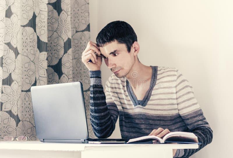 年轻人画象便衣的在看与周道的面孔的膝上型计算机的工作工作 免版税图库摄影