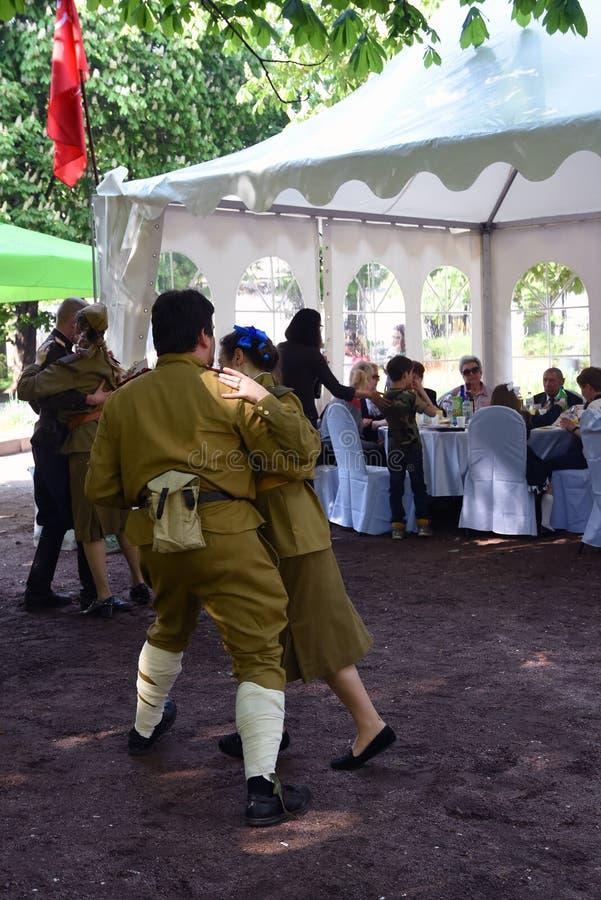 年轻人画象军服的,他们跳舞 库存照片
