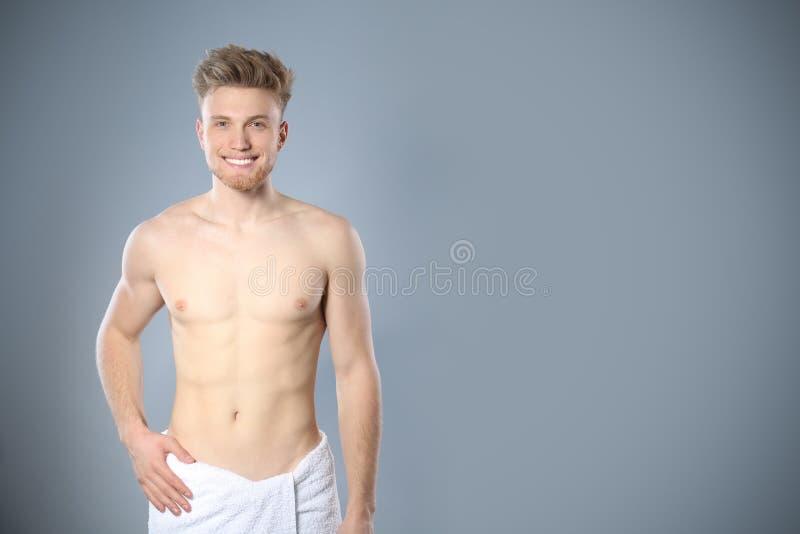 年轻人画象有亭亭玉立的身体的在灰色背景的毛巾 免版税库存照片