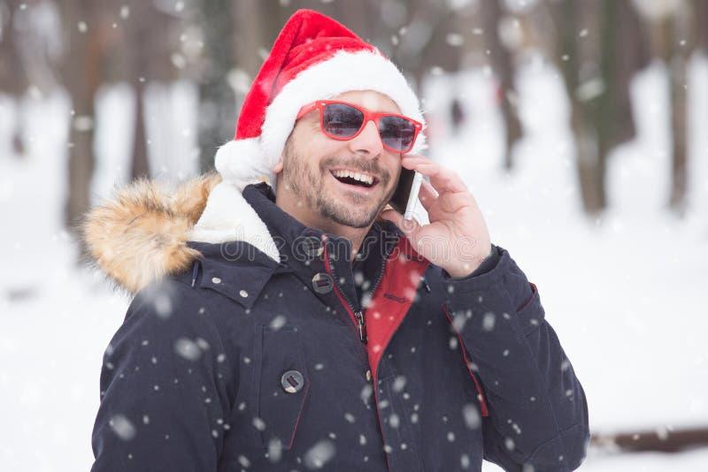 年轻人画象有圣诞老人帽子的在雪天谈话在smar 图库摄影