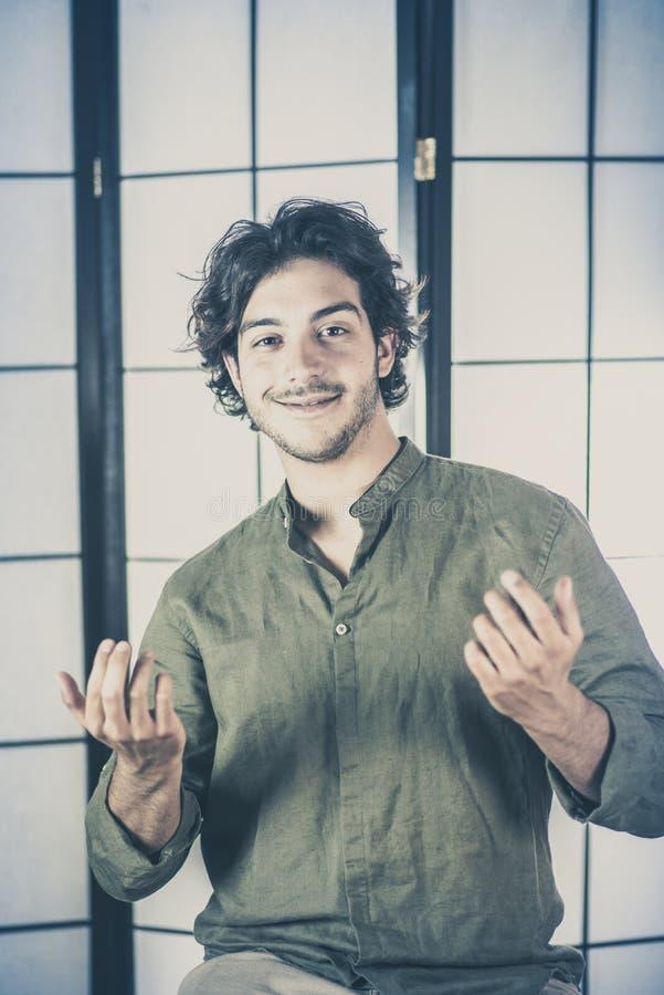 年轻人画象用在胸口的被举的手 免版税库存照片