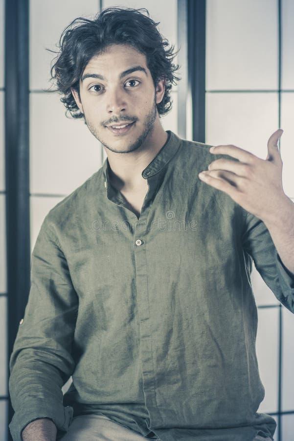年轻人画象用在胸口的被举的手 免版税图库摄影