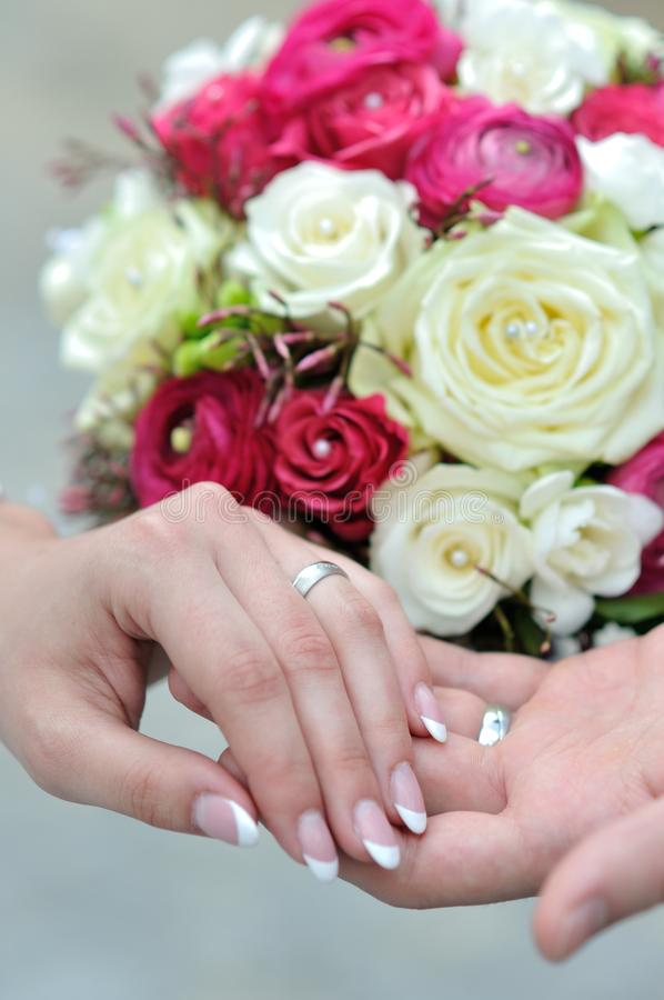 年轻人的手与夫妇和婚礼花束结婚 库存图片