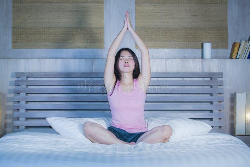 年轻人相当亚裔中国妇女在家放松卧室的20s或30s坐在莲花瑜伽位置的床在凝思和放松 库存图片