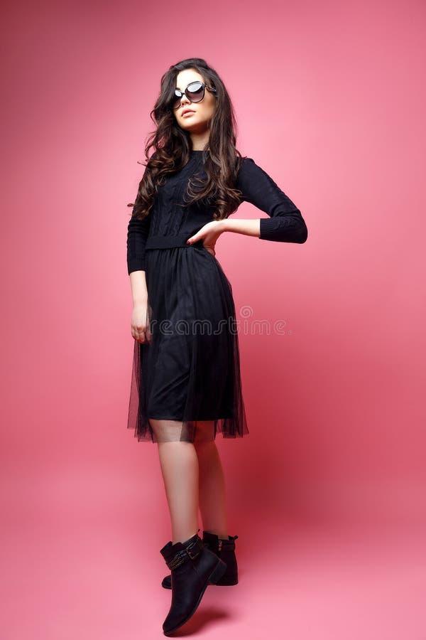 年轻人相当性感的妇女或女孩有逗人喜爱的面孔和长的深色的头发的有时兴的构成在黑礼服在桃红色 免版税库存图片