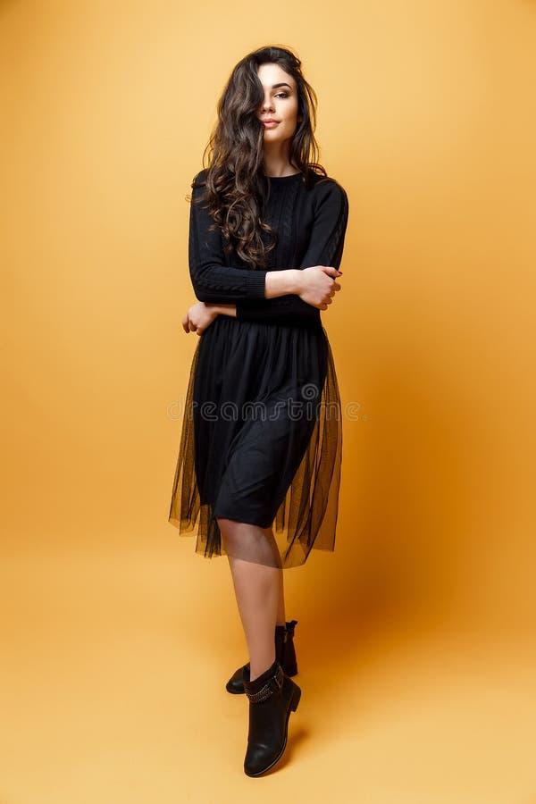 年轻人相当性感的妇女或女孩有逗人喜爱的面孔和长的深色的头发的有时兴的构成在黑礼服在黄色 库存照片
