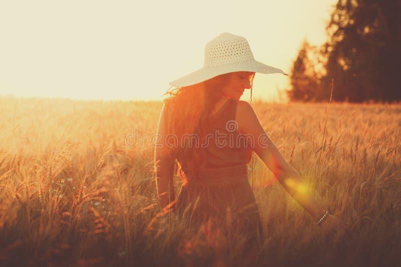 年轻人相当滑稽的微笑的女孩画象夏天天气的在麦田的背景的明亮的帽子穿戴了 库存照片